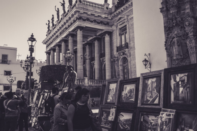 Black and white photo of an art exhibit in the street of Irapuato, in Mexico. In the background, there is the opera and in the foreground people looking at the paintings.