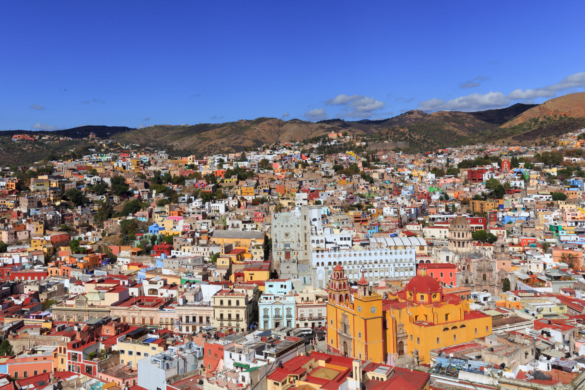 Photo of the city of Guanajuato in Mexico. Multi colored buildings and houses with the mountain behind.