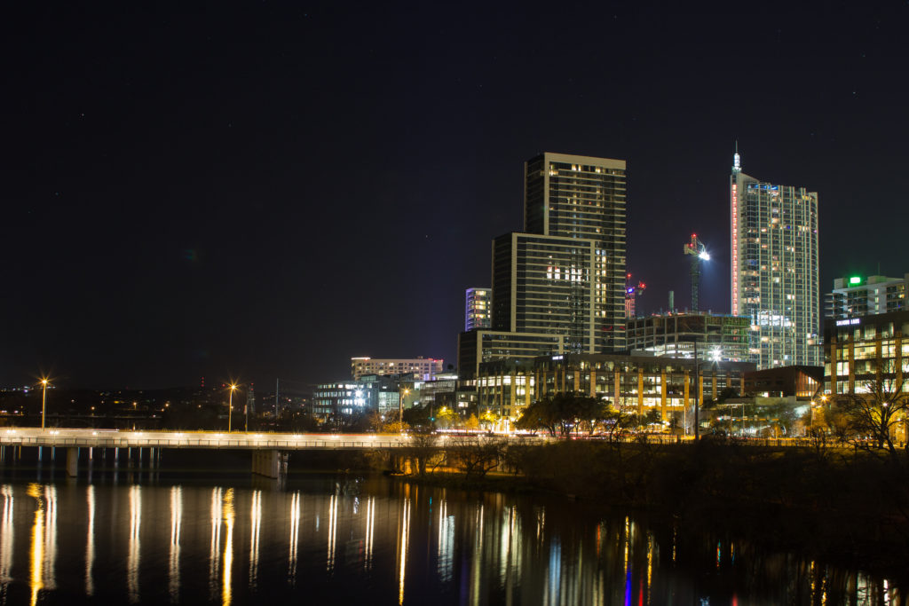 Night view of Austin, Texas downtown with building in the background and water in the foreground