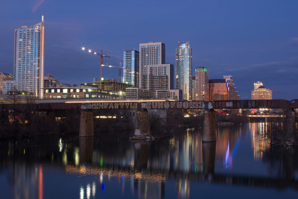 Night view of Austin, Texas downtown with building in the background and a bridge in the foreground