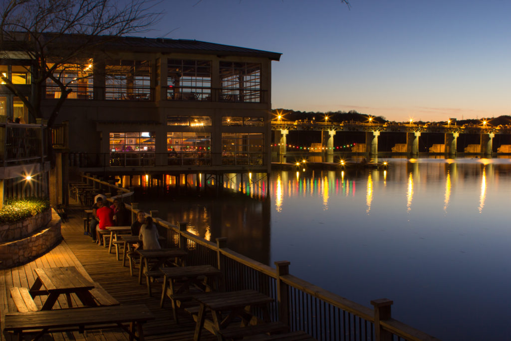 Photo of the view from Mozart Coffee in Austin, Texas just before dusk where you can see in the foreground people sitting at tables and hanging out and in the background, a bridge.