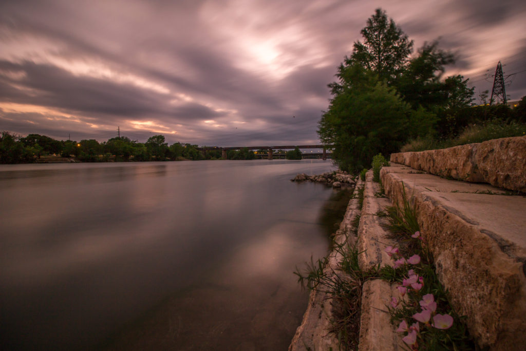 Sunset of Town Lake in Austin, Texas . In the foreground, there are rocks and in the background a bridge. Clouds are heavy and low.