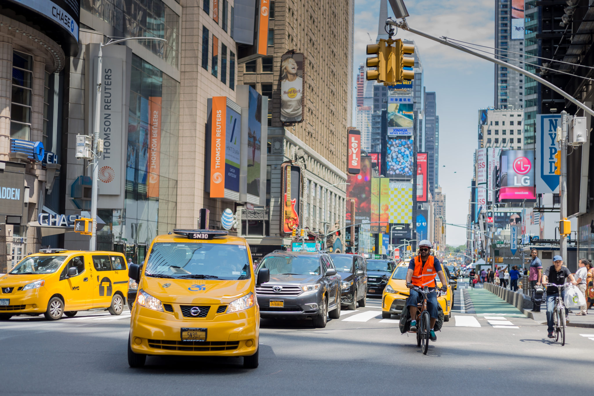 Photo of a New York street next to Time Square. People riding, walking on the sidewalk. Cars and taxis driving are about to turn right. Huge buildings with commercials promoting LG, Chase,...