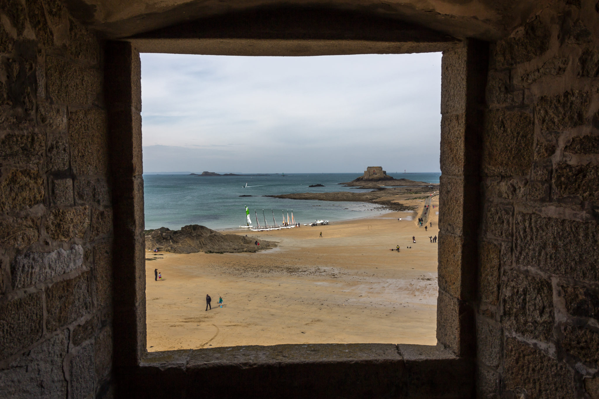 Photo of a window where we see the sea, sailing ships and rock