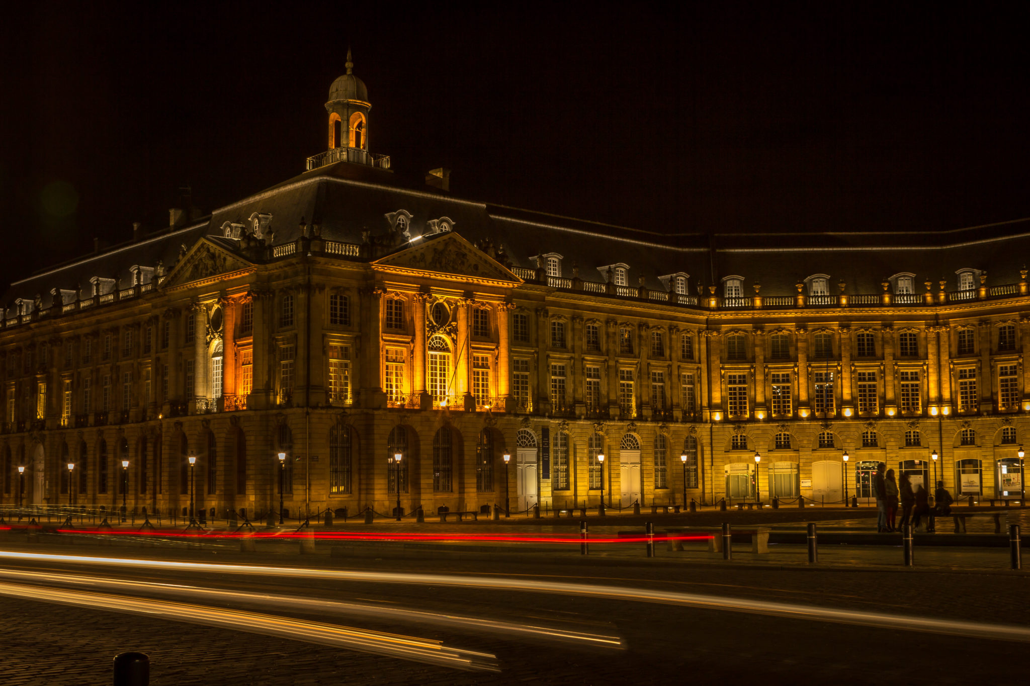 Night photo of Place de la Bourse in Bordeaux, France. Illuminated building. Red and yellow car lights in the foreground because of the long exposure.
