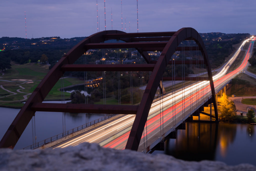 night photo of cars over the 360 bridge in Austin, Texas